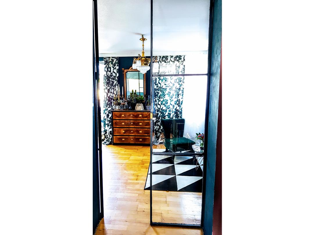 Blick ins Wohnzimmer durch Tür aus Glas und Stahl